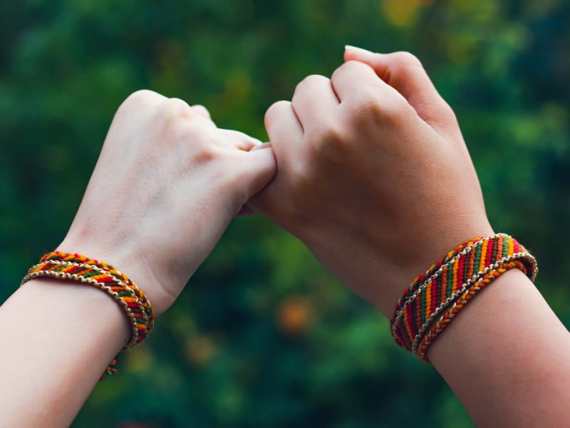 two children wearing friendship bracelets made with string